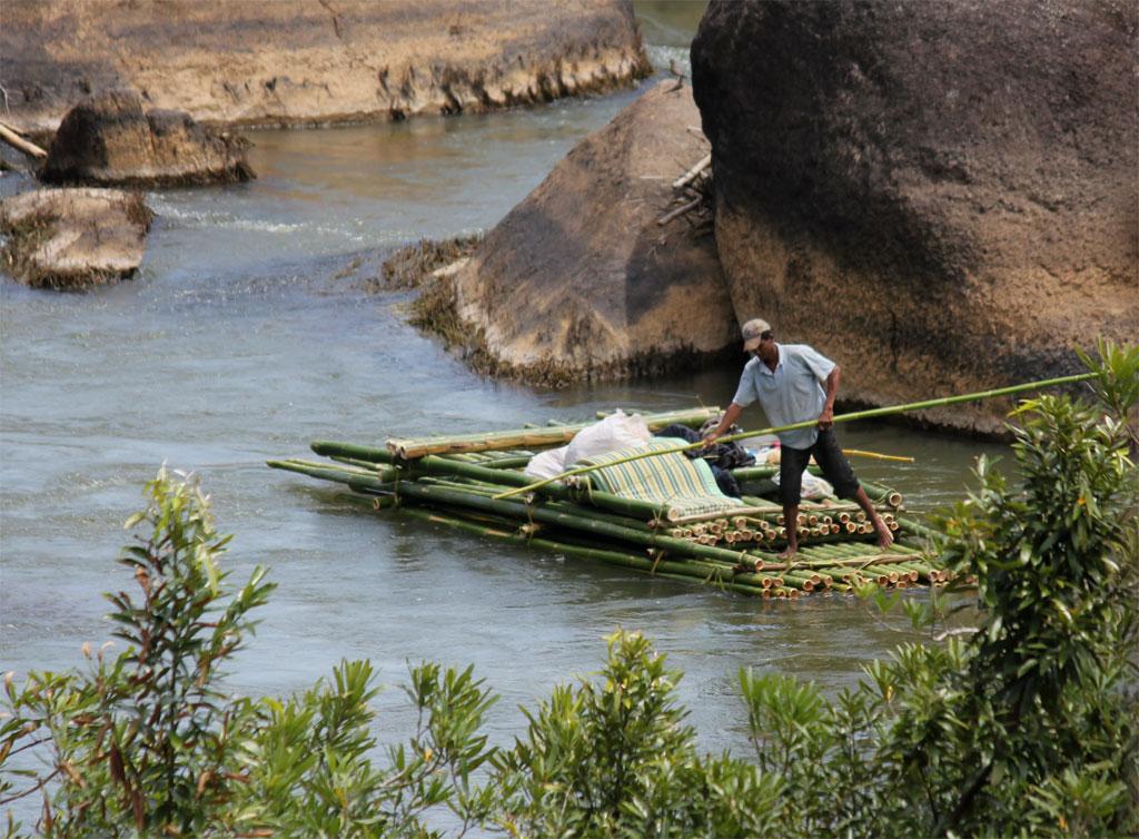 De vlotbeheerder voert alleen het bamboevlot door de stroomversnellingen