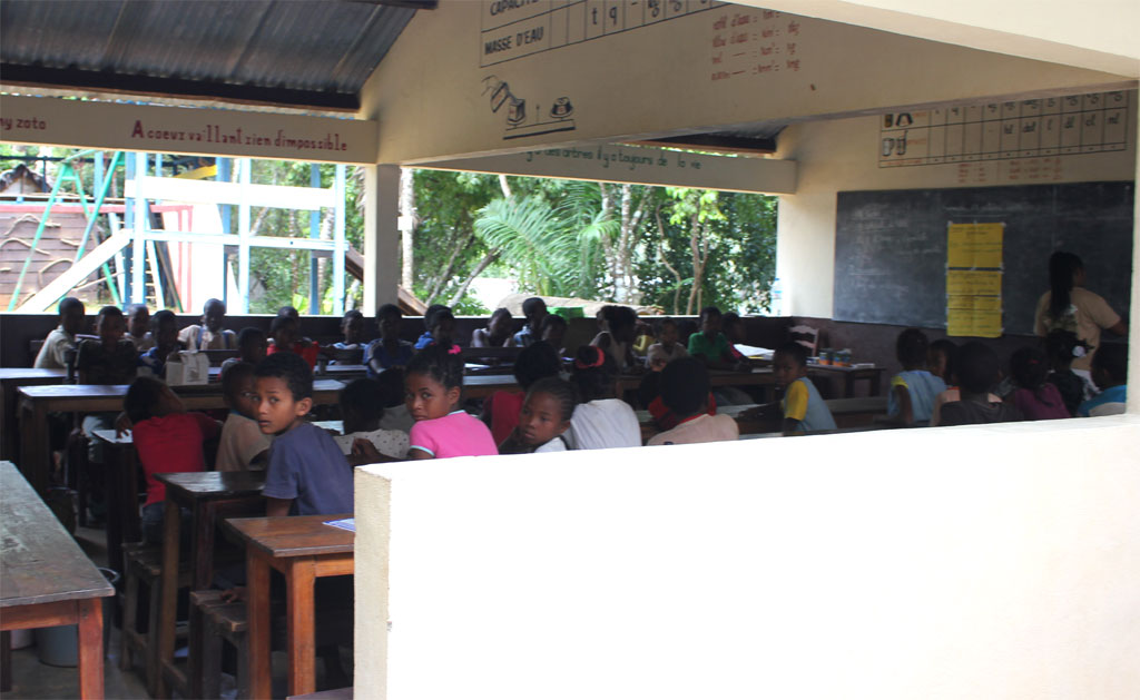 Een groep kinderen krijgt les in een open klaslokaal